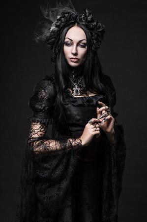 スタジオで暗いドレスで美しいゴシック女性の肖像画