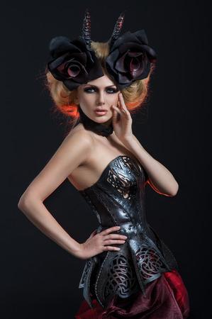 sexy vampire: Portrait of beautiful blond woman in dark sexy corset in studio