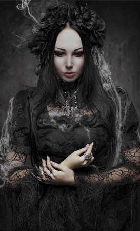 scared woman: Portrait of beautiful Gothic woman in dark dress in studio