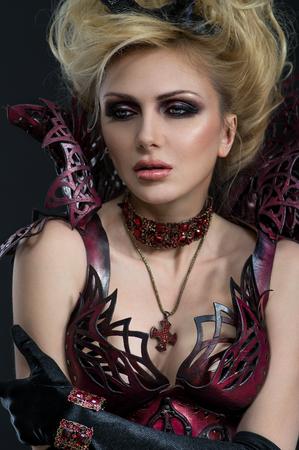 Portrait of beautiful devil woman in dark sexy dress in studio