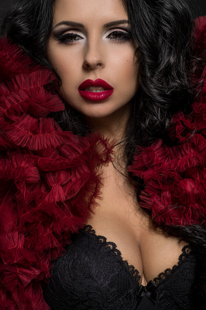 sexy photo: Sexy brunette woman in black underclothes and red fluffy bolero on dark background