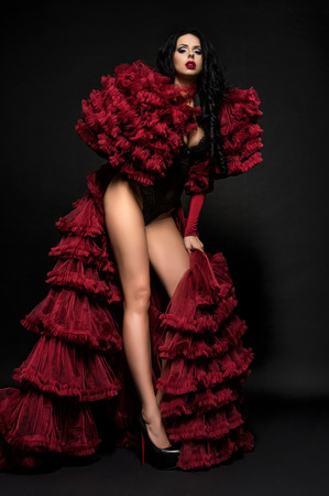 Sexy brunette woman in black underclothes and red fluffy bolero on dark background