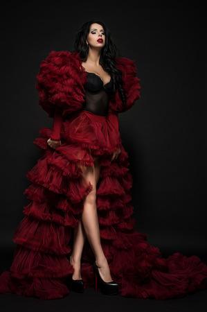 bolero: Sexy brunette woman in black underclothes and red fluffy bolero on dark background