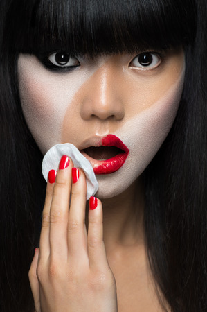 Asian woman removing make-up