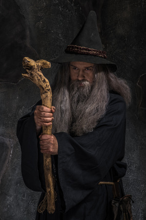 Stary czarownik z drewnianym pracowników