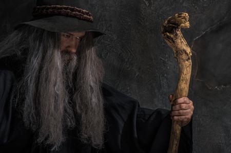 Oude tovenaar met een houten staf Stockfoto