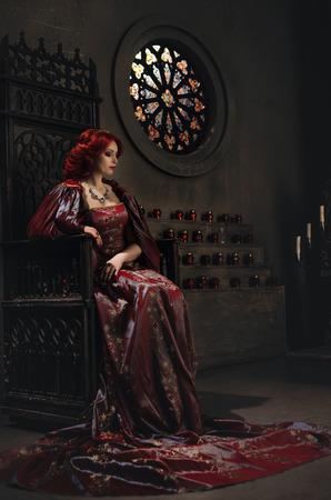 castillos de princesas: Mujer con el pelo rojo que lleva elegante atuendo real y su corona de oro sentado en un trono en el antiguo castillo Foto de archivo