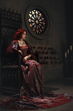 queen's theatre: Woman with red hair wearing elegant royal garb and golden crown sitting on a throne in ancient castle Stock Photo