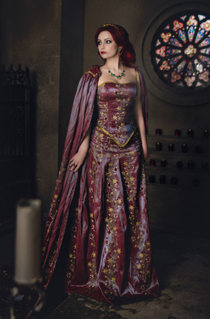 garb: Woman with red hair wearing elegant royal garb and golden crown in ancient castle