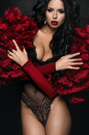 underclothes: Sexy brunette woman in black underclothes and red fluffy bolero on dark background