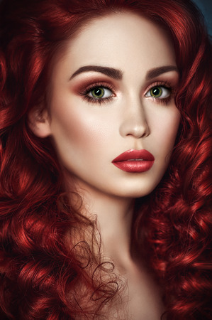 long curly hair: Portrait of beautiful redhead woman with wavy hair and green eyes looking at camera
