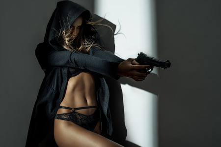 glamour nude: Beautiful woman in a luxurious lingerie and hood with a gun Stock Photo