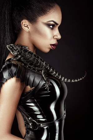 Sexy woman in black latex outfit with lizard on her shoulder Stock fotó