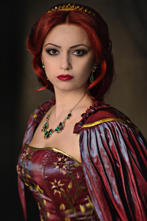 Woman with red hair wearing elegant royal garb and golden crown