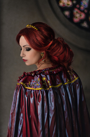 red hair girl: Woman with red hair wearing elegant royal garb and golden crown