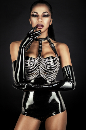 latex fetish: Portrait of sexy woman in black latex outfit with metal chains Stock Photo
