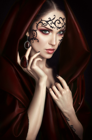 Beauty portrait with lace face-art in red cloak with hood