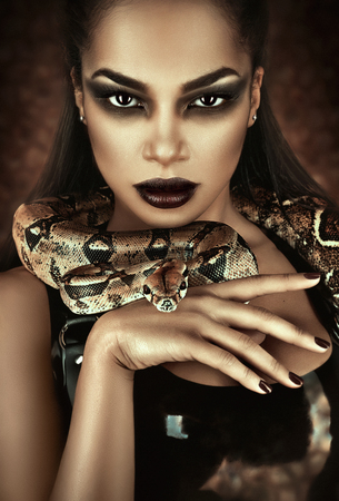 serpent: Close up portrait of sexy woman with snake in latex outfit Stock Photo