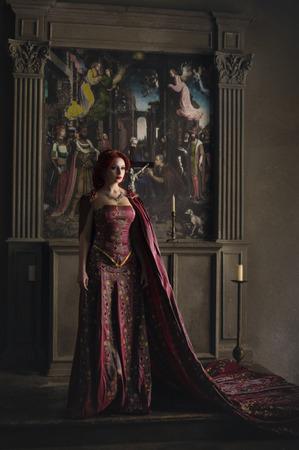 고대의 성에서 빨간 머리 입고 우아한 왕실 복장 및 황금 왕관을 가진 여자