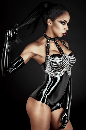 gothic fetish: Portrait of sexy woman in black latex outfit with metal chains Stock Photo