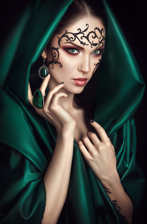 faceart: Beauty portrait with lace face-art in green cloak with hood