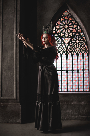 garb: Woman with red hair wearing elegant royal garb and crown in ancient castle