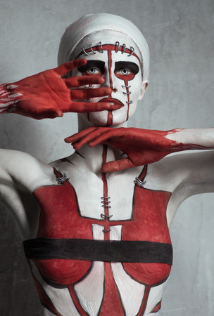 lady hand: Model with creative red and white body art on cement wall background