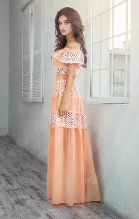 Woman near the window in pink dress