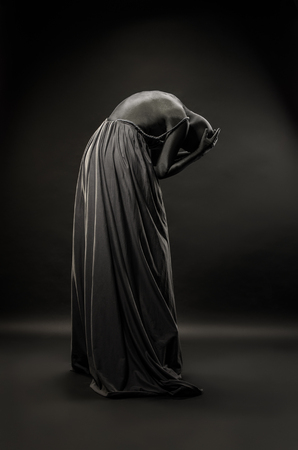 Woman wrapped in black robes Stock Photo