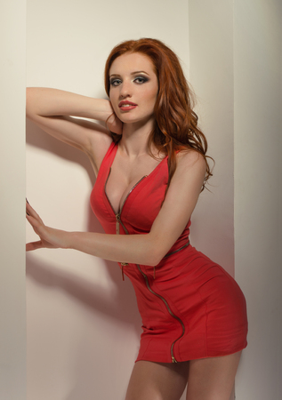 Sexy redhead woman posing in a red dress