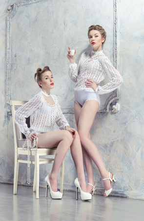 Two pretty women in white costumes posing in white room