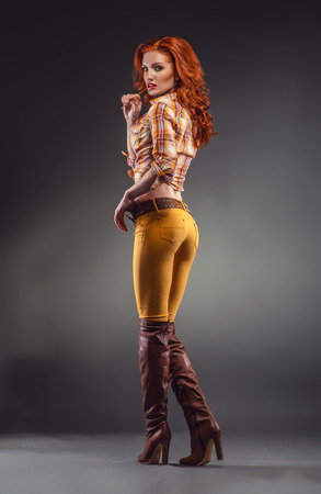 Fashion shot of sexy redhead woman in stylish outfit Banque d'images