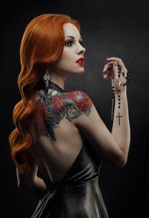 Posh redhead woman in black dress 写真素材