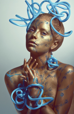 bodyart: Woman with golden body-art and blue tubes