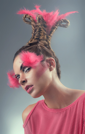 vibrancy: Beauty portrait of young woman with pink feathers and hairstyle Stock Photo