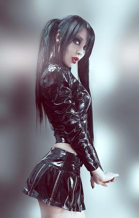 Retrato gótico del estudio de la mujer atractiva morena en traje de vinilo negro