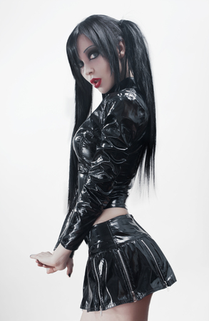 minifalda: Retrato gótico del estudio de la mujer atractiva morena en traje de vinilo negro Foto de archivo