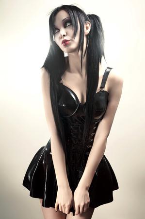 Gothic studio portrait of brunette sexy woman in black latex dress Stock Photo