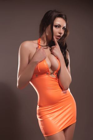 Sexy lady in orange fetish dress Stock Photo
