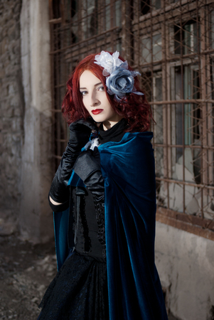 velvet dress: Gothic redhead woman walking with candle Stock Photo