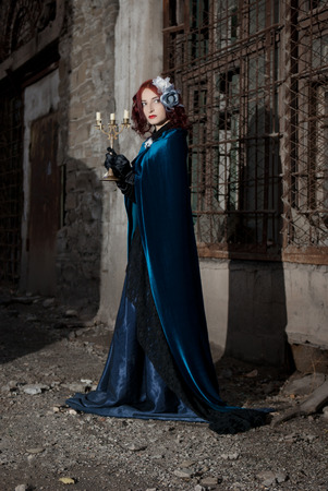 Gothic redhead woman walking with candle Фото со стока