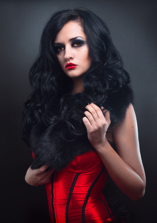 red corset: Sexy brunette in red corset fur and long hair in studio Stock Photo