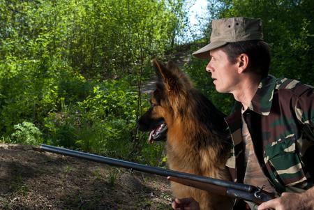 ambush: Hunter with dog in rifle. Ambush