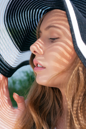 black shadow: Closeup portrait of young blond woman wearing black and white summer hat