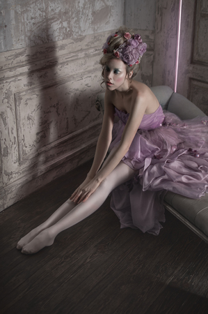 feminine background: Girl in purple dress and flowers in hair posing in old room