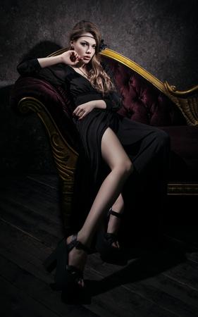 Sexy giovane donna in abito nero disteso sul divano rosso epoca