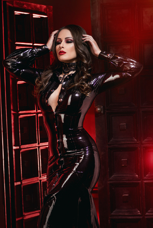 Confident woman in black latex dress posing on red doors background