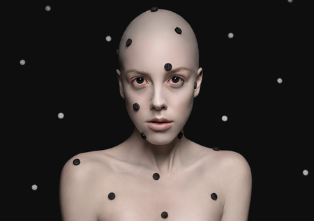 bald girl: Bald headed girl with dots on face on dotted black background
