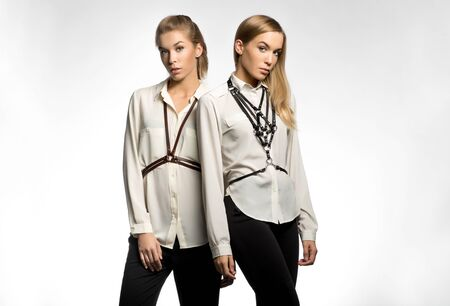 blouses: Two models in blouses with sword belts on white background Stock Photo