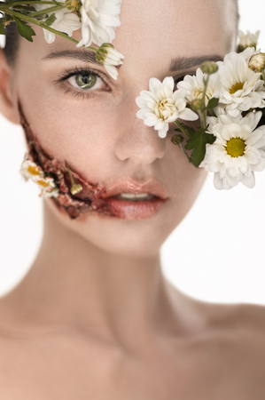 cheek: Beauiful girl with huge wound on cheek and flowers covering face